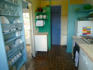 6) Cuisine, vue vers la salle de douche et la buanderie (machines à lavé/sèche linge